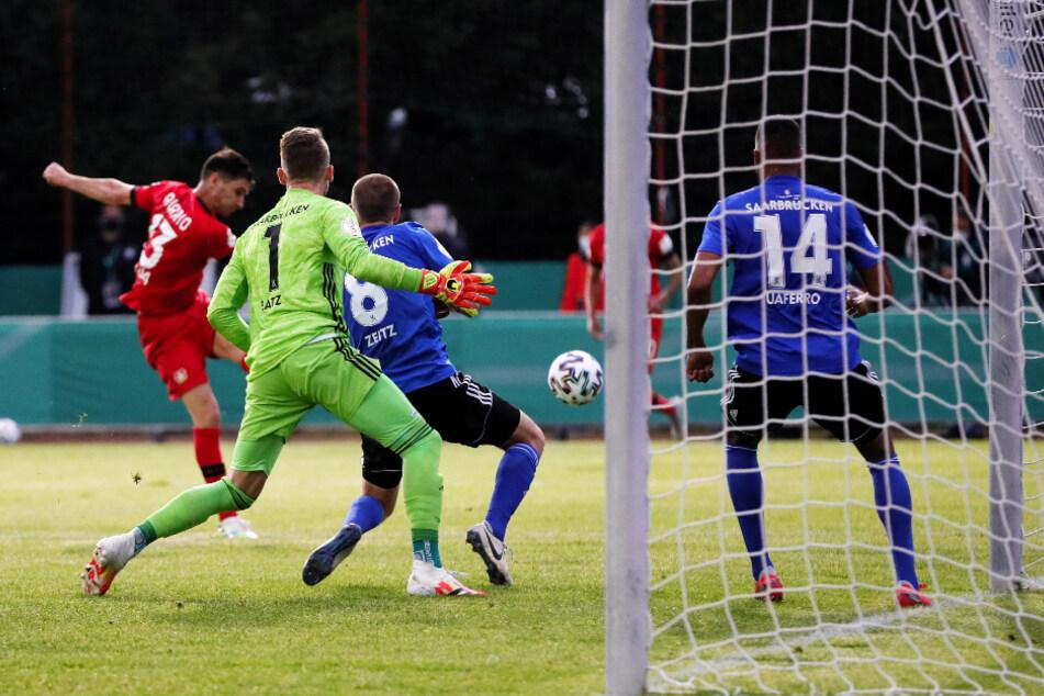 Leverkusens Stürmer Lucas Alario (rotes Trikot) trifft an allen Saarbrücker Abwehrspielern vorbei zum 2:0 für Bayer.