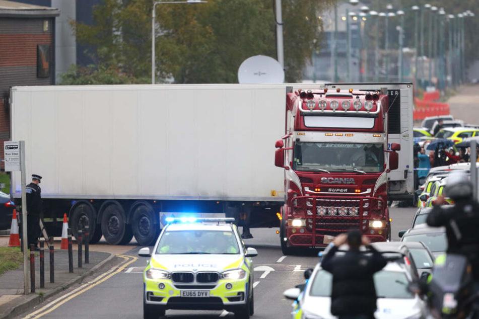 Ein Polizeiauto eskortiert den LKW, in dem 39 Leichen gefunden worden waren, beim Verlassen des Waterglade Industrieparks.