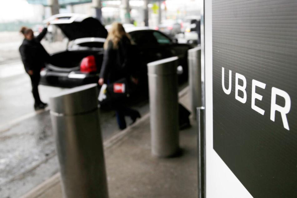 Eine Uber-Fahrerin hält den Kofferraum für einen Fahrgast auf (Symbolbild).