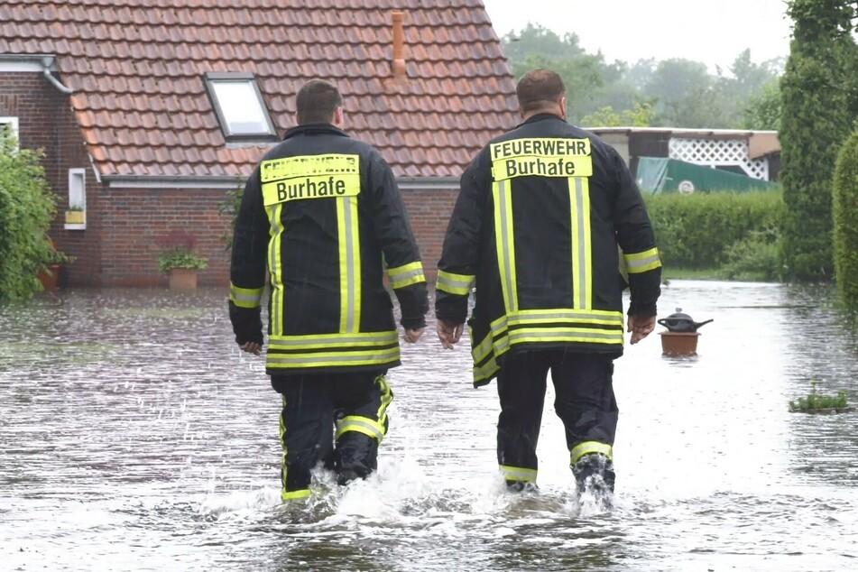 Feuerwehrleute gehen durch eine der überfluteten Straßen.