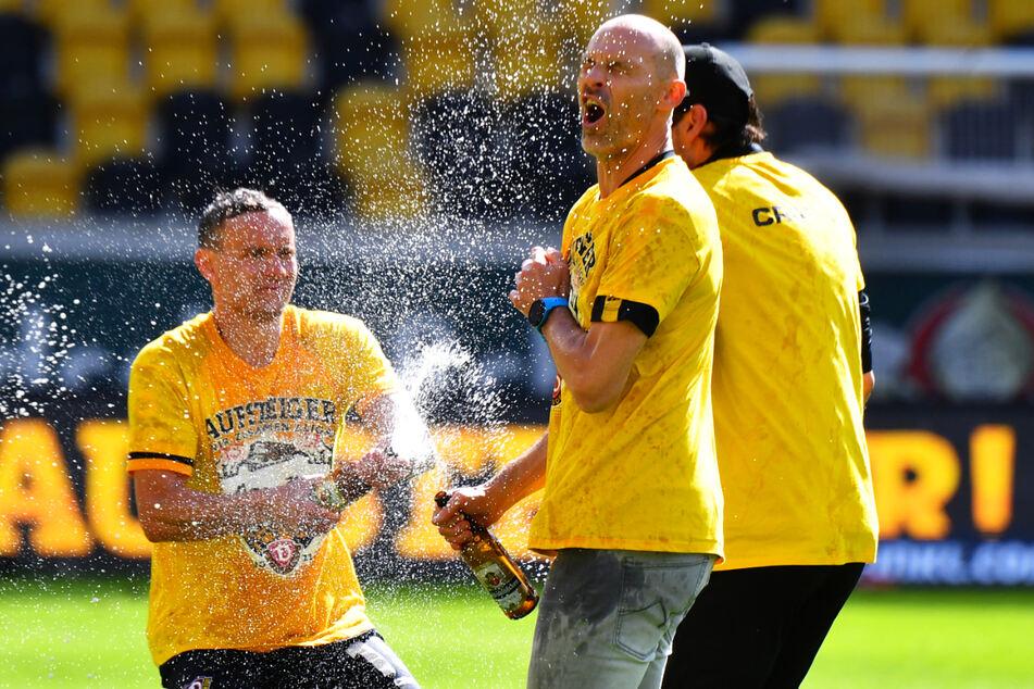 Ausgelassener Jubel: Nach dem geschafften Aufstieg gab es von Chris Löwe (32, l.) die Bierdusche für Coach Alexander Schmidt (52, M.).