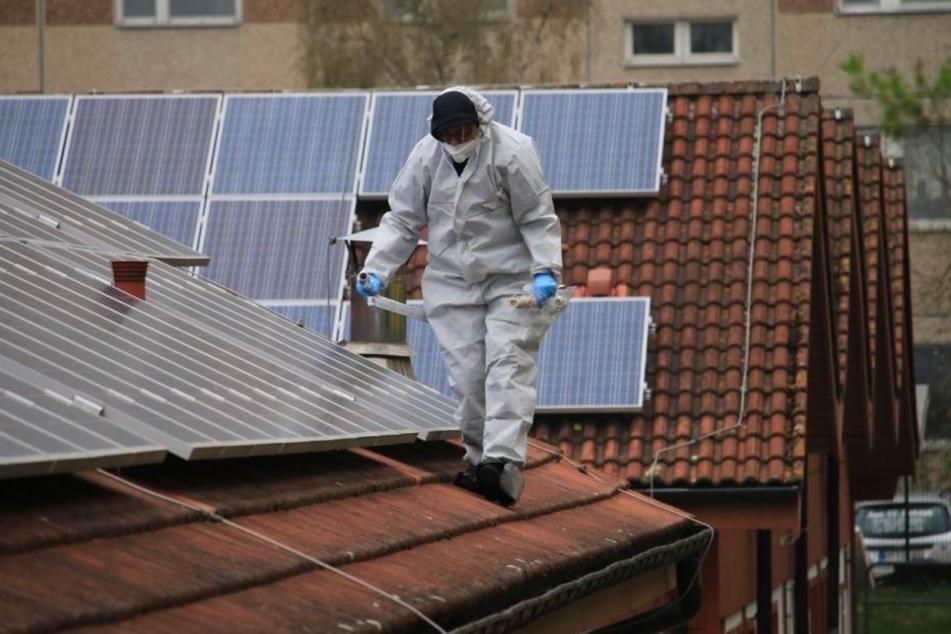 Ein Mitarbeiter der Spurensicherung sucht das Dach der Unterkunft ab.