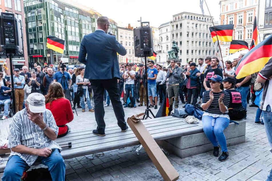 """Dennis Augustin, Kreisvorsitzender des AfD Landesverbandes Südwest-Mecklenburg, spricht vor den Teilnehmern der """"Merkel muss weg!"""" Kundgebung auf dem Gänsemarkt."""