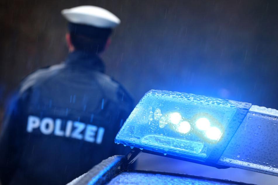 Ein Polizist steht im Regen vor einem Streifenwagen dessen Blaulicht aktiviert ist.