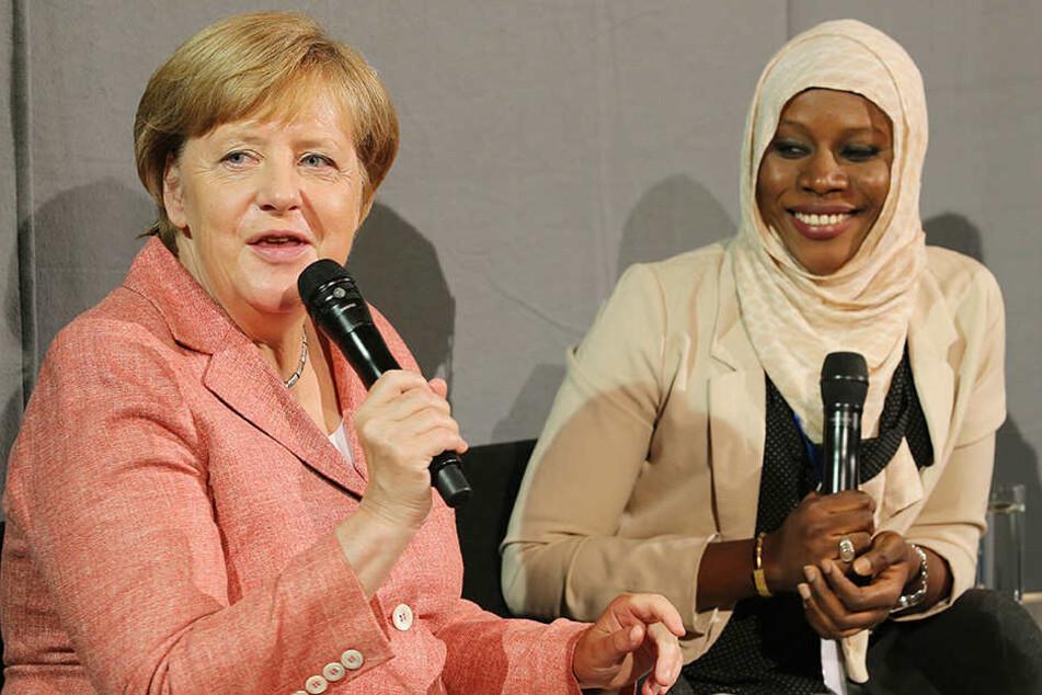 Bundeskanzlerin Angela Merkel das Berliner Start-Up-Unternehmen Kiron und unterhält sich mit Nyima Jadama, Flüchtling aus Gambia, die bei Kiron Politikwissenschaften studiert.