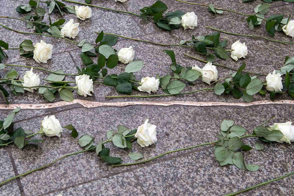 Weiße Rosen liegen bei der Einweihung der Gedenkstätte an der Gedächtniskirche auf den Boden.