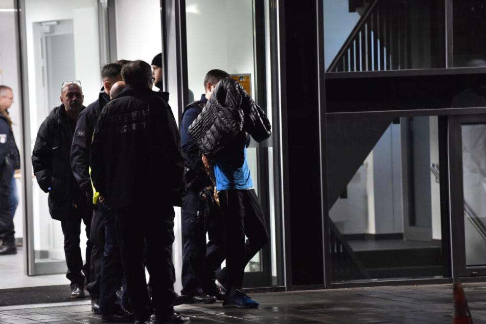 Polizisten nehmen nach der Messerattacke einen Mann fest.