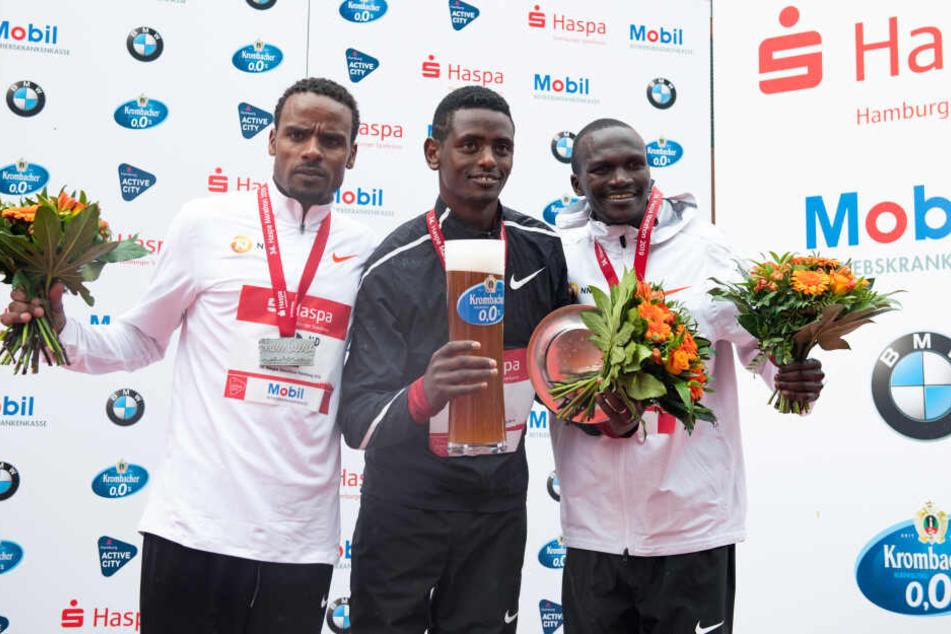 Marathon-Sieger Tadu Abate (Mitte) aus Äthiopien jubelt beim 34. Hamburg Marathon bei der Siegerehrung, links steht der zweitplatzierte Ayele Abshero aus Äthiopien und rechts der drittplatzierte Stephen Kiprotich aus Uganda.