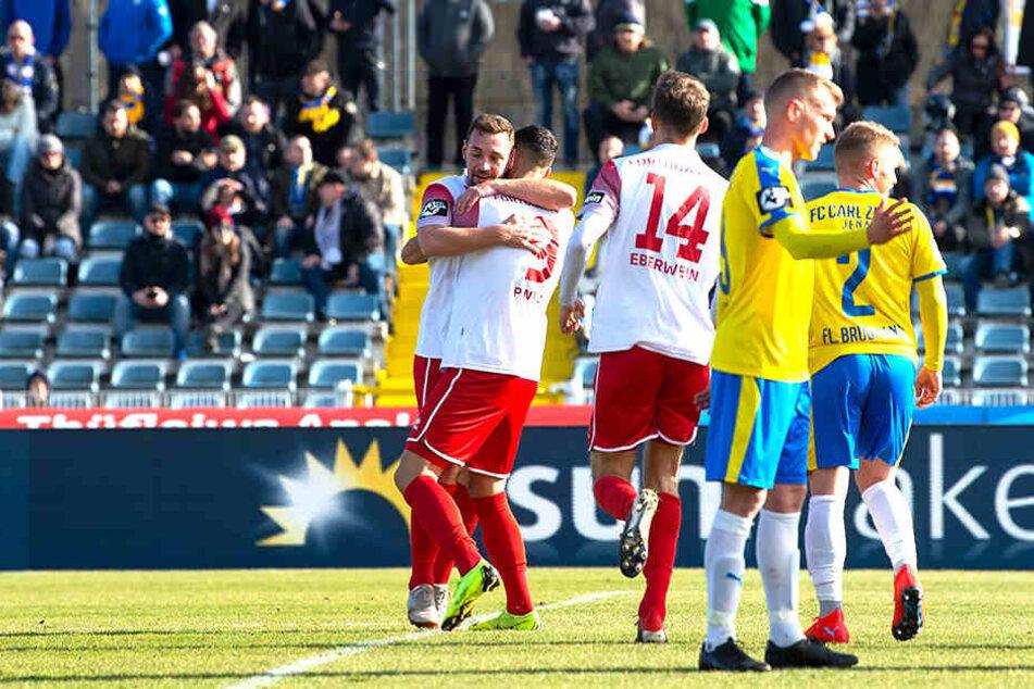 Während Maik Kegel über seinen Führungstreffer jubelt und die Mitspieler gratulieren, machen sich die Mitspieler von Carl Zeiss Jena Mut.