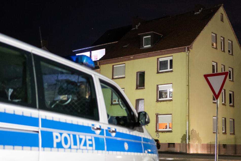 Ein Streifenwagen der Polizei steht vor dem Mehrfamilienhaus, in dem zuvor Durchsuchungen stattgefunden haben.