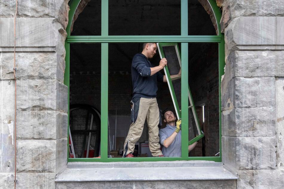 Die Tischler Felix Günzel (21, l.) und Alexander Kroner (35) bauen im Erdgeschoss die letzten Fenster ein.
