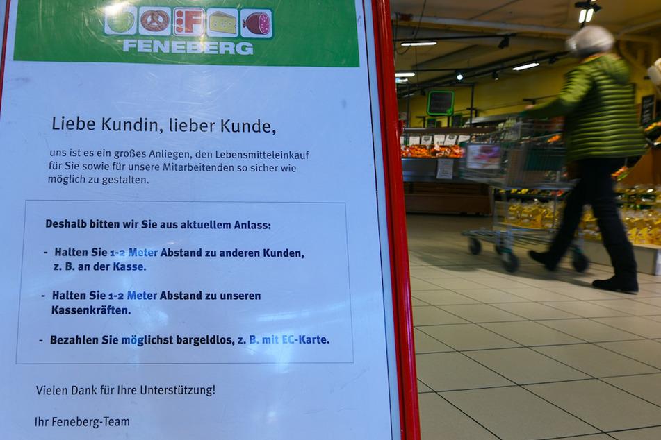 Ein Schild weist in einem Supermarkt auf die richtigen Verhaltensregeln beim Einkaufen hin.