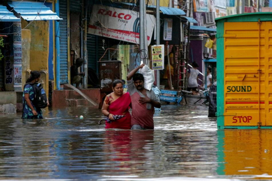 Chennai: Menschen waten durch eine überflutete Straße.