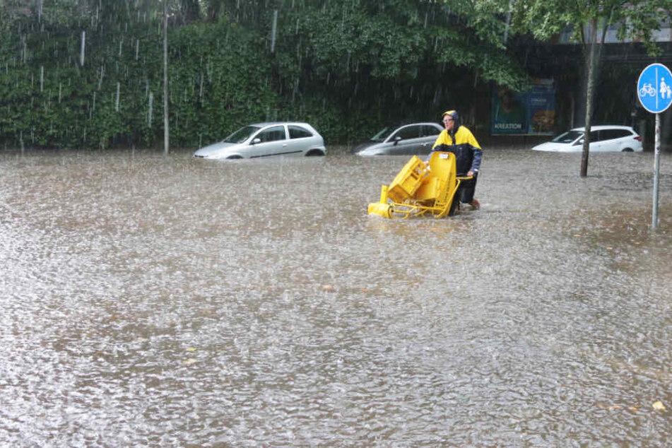 Ein Postbote kämpft sich durch die überflutete Straße in Flensburg.