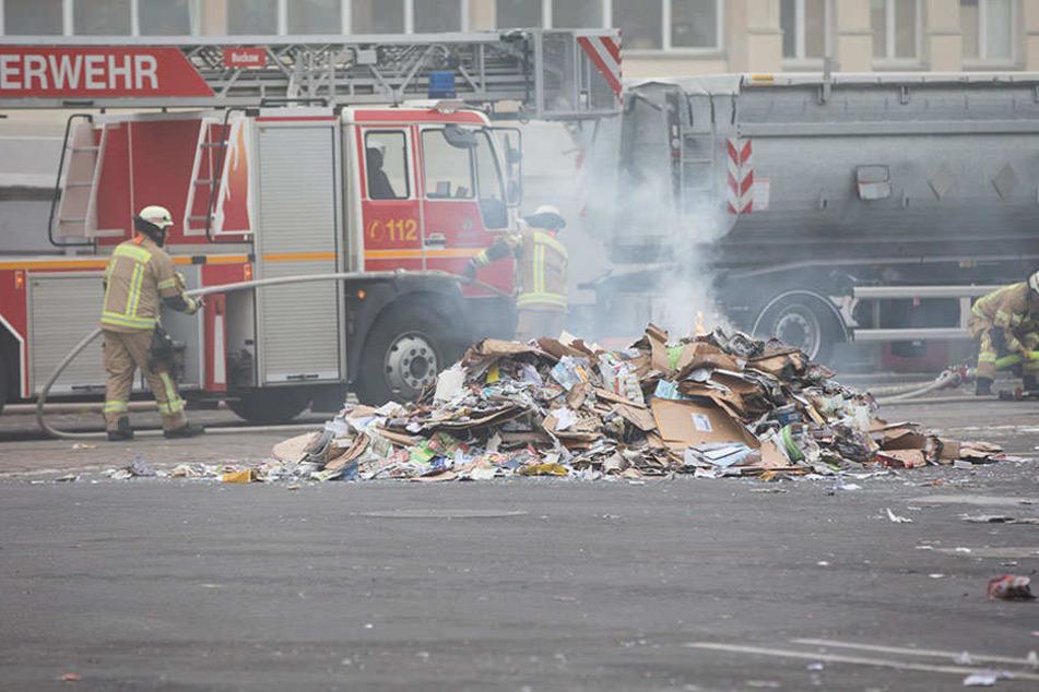Feuerwehrkräfte löschen gezielt die aufgeschütteten Papierhaufen.