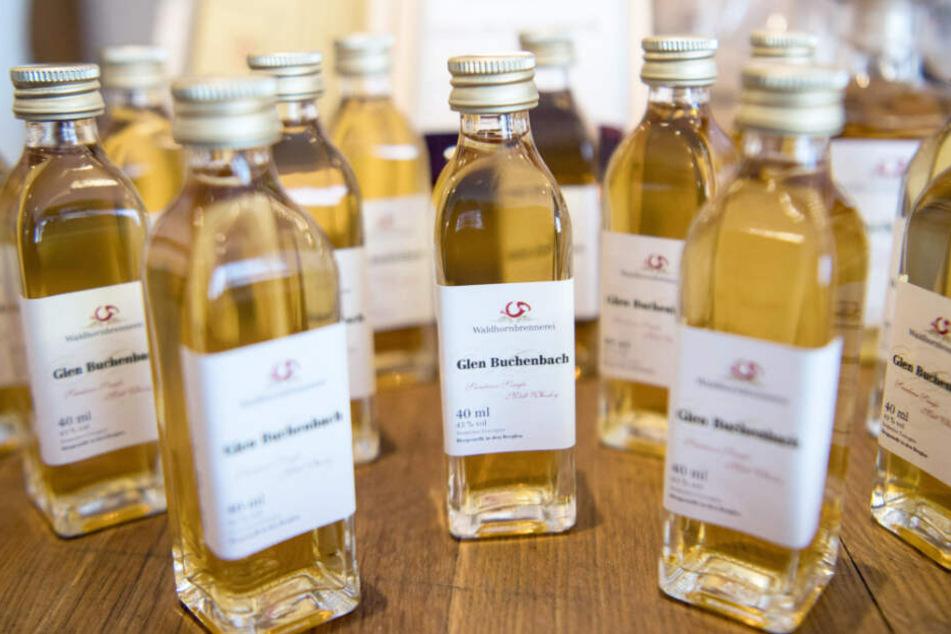 """Mehrere Whisky-Flaschen mit der Aufschrift """"Glen Buchenbach"""" stehen auf einem Tisch. Sie müssen jetzt umbenannt werden."""