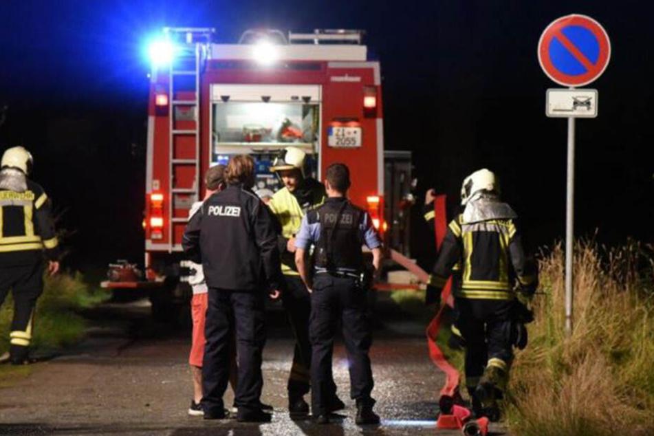 Die Polizeibeamten und die Feuerwehrleute sprechen mit dem Eigentümer.