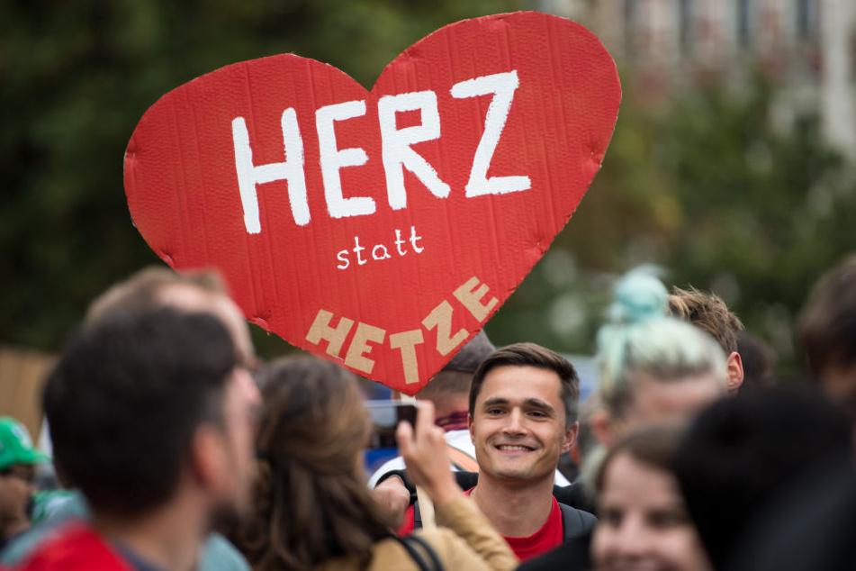 """Ein Demo-Teilnehmer hält ein Schild mit dem Schriftzug """"Herz statt Hetze""""."""