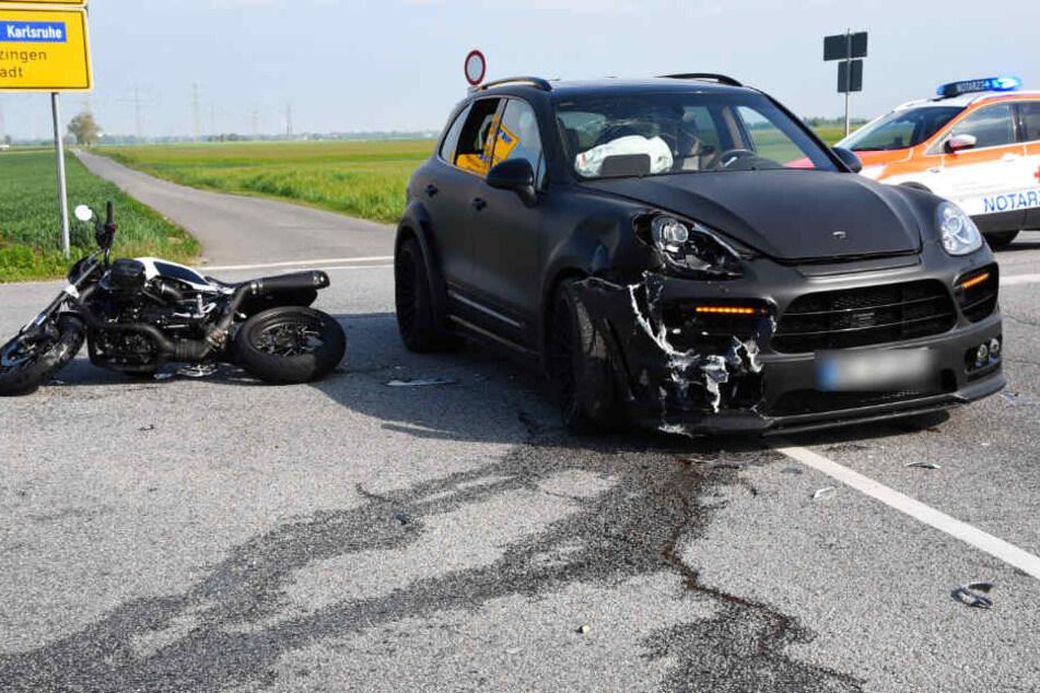 Ein Notarzt an der Unfallstelle, neben dem Motorrad und verunfallten Porsche.