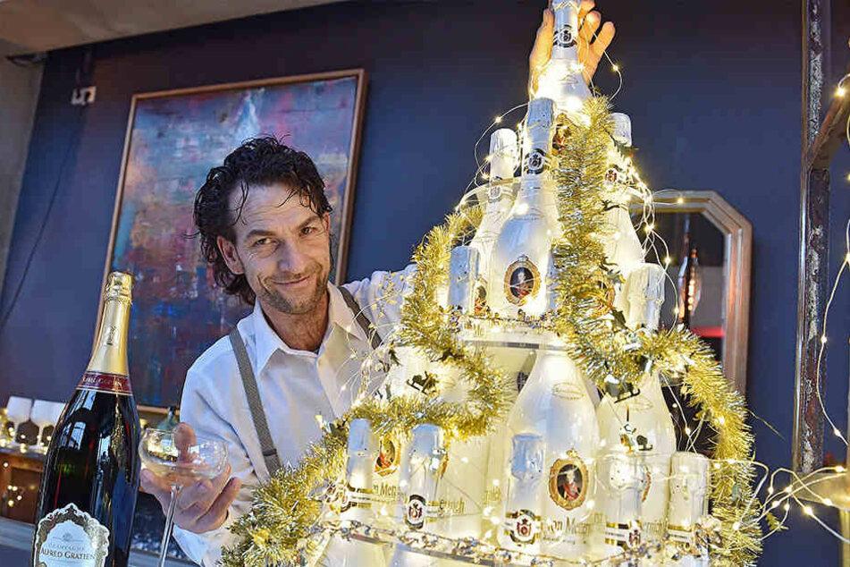Gastgeber René Kuhnt (49) türmt auf der verspiegelten Bar eine große Sektpyramide auf.