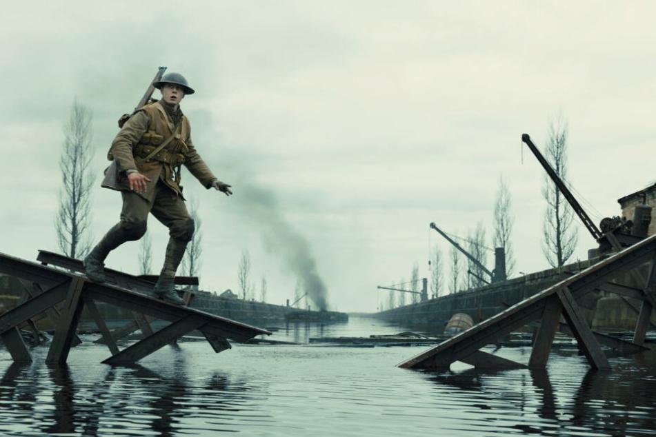 Schofield (George MacKay) balanciert auf einem Geländer einer kaputten Brücke.