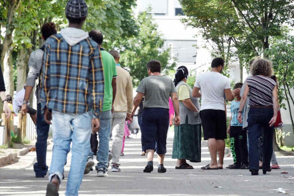 Flüchtlinge gehen vor der Landeserstaufnahme für Asylbewerber (LEA) in Karlsruhe.