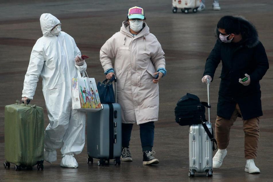 Bahnreisende in China mit Schutzkleidung. (Archivbild)