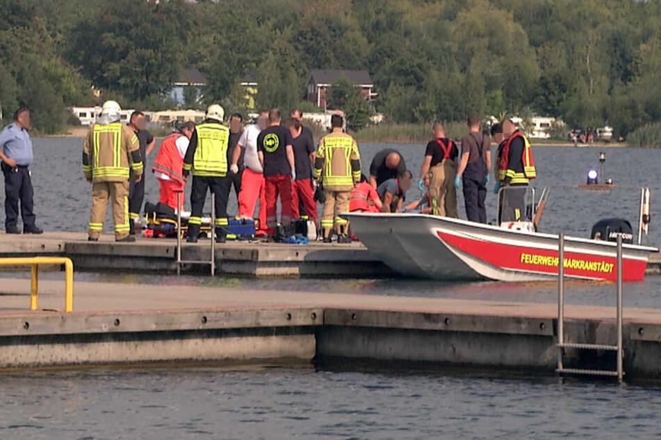 Auf der Steganlage des Segelclubs kümmern sich Rettungskräfte um die entkräfteten Männer.
