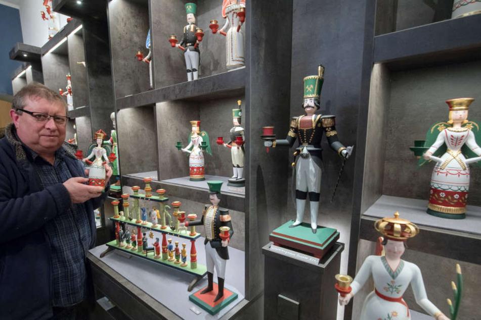 Gunnar Horatzscheck steht in seinem Laden in Annaberg-Buchholz vor einem Regal mit einer Auswahl seiner Figuren nach traditionellen Entwürfen.