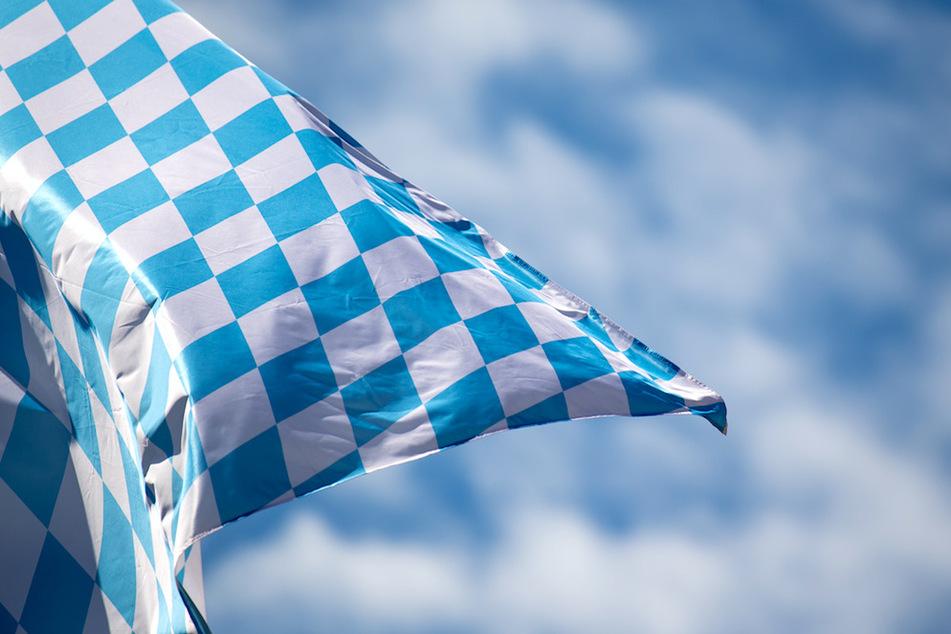 Die bayerische Flagge mit weiß-blauen Rauten weht vor weiß-blauem Himmel im Wind. (Symbolbild)