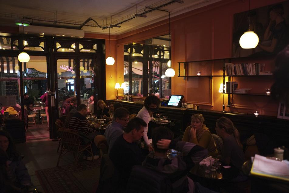 Menschen sitzen an Tischen in einem Restaurant in Paris.