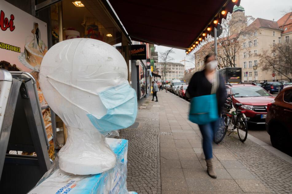 Eine medizinische Maske wird vor einem Geschäft in Berlin-Neukölln ausgestellt, während eine Passantin vorbeigeht.