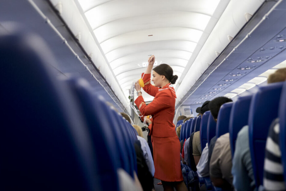 Eine Flugbegleiterin gibt in der Kabine Sicherheitseinweisungen an die Fluggäste (Symbolbild).