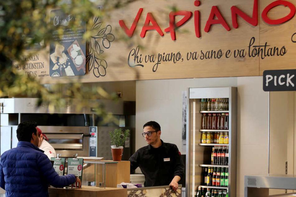 Ein Mitarbeiter bedient in einer Filiale der Restaurantkette Vapiano einen Kunden (Archivbild).