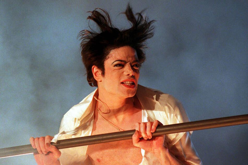 """4.11.1995, Duisburg: Michael Jackson steht mit wehenden Haaren und singend bei """"Wetten, dass ..?"""" am Geländer einer Hebebühne, mit der er über die Zuschauer der Rhein-Ruhr-Halle geschwenkt wird."""