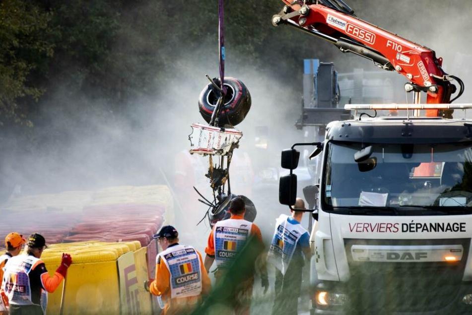 Streckenposten bringen die völlig zerstörten Reste der Unfallautos von der Strecke.