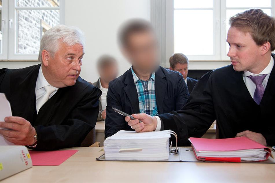 Der Polizist Stephan S. zwischen seinen Verteidigern. Im Hintergrund sieht man den ebenfalls Angeklagten Polizisten Lars W..
