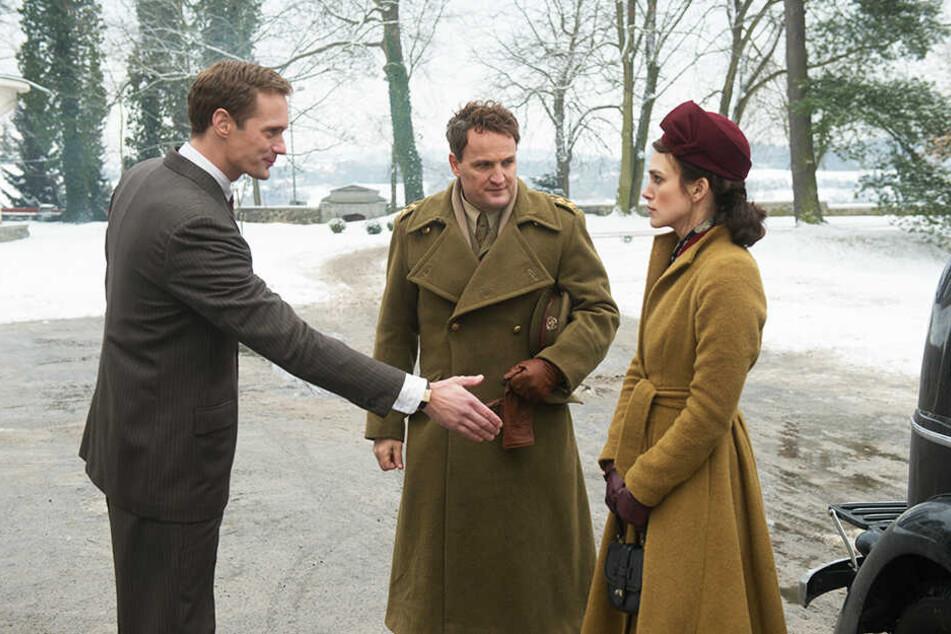 Rachael Morgan (r., Keira Knightley) und ihr Mann Lewis (M., Jason Clarke) werden von Stephan Lubert (Alexander Skarsgård) willkommen geheißen.