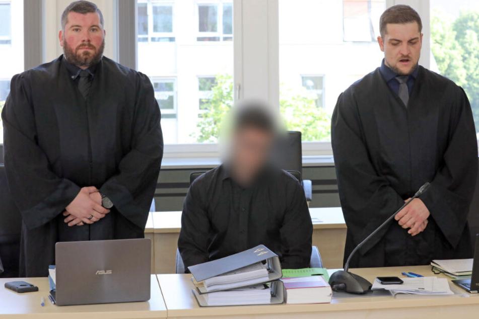 Der Angeklagte sitzt zwischen seinen beiden Verteidigern.