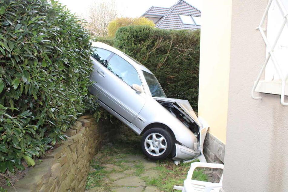 Senior kracht mit Auto gegen Hauswand