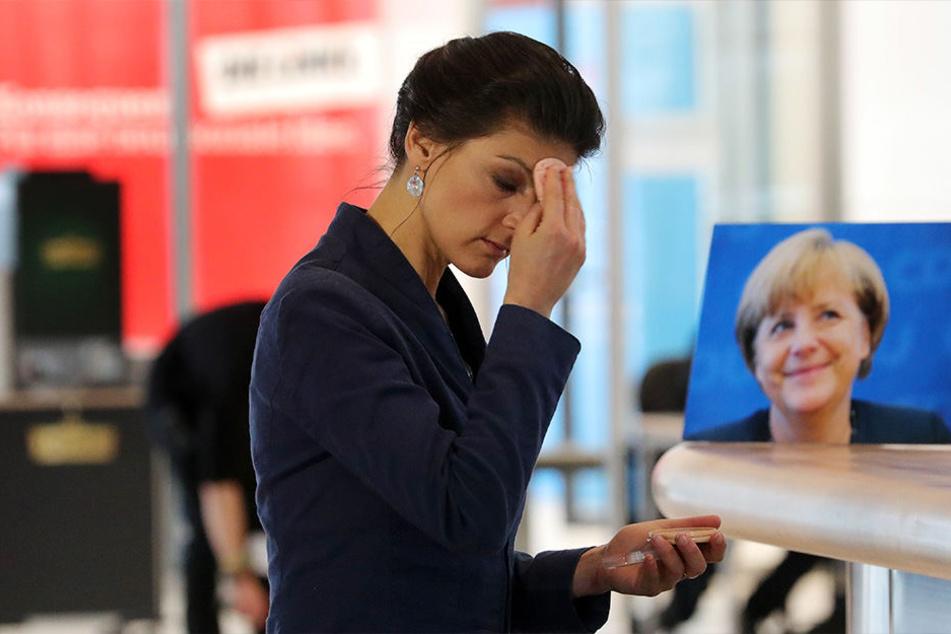 Sahra Wagenknecht, Vorsitzende der Bundestagsfraktion der Partei Die Linke. Hinter ihr auf einem Tisch steht das Portrait der Bundeskanzlerin.