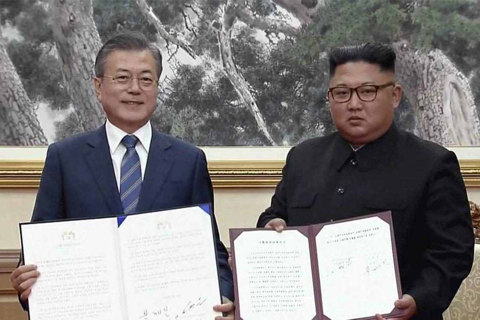 Moon Jae In (l), Präsident von Südkorea, und Kim Jong Un, Machthaber aus Nordkorea, zeigen die unterzeichneten Dokumente.