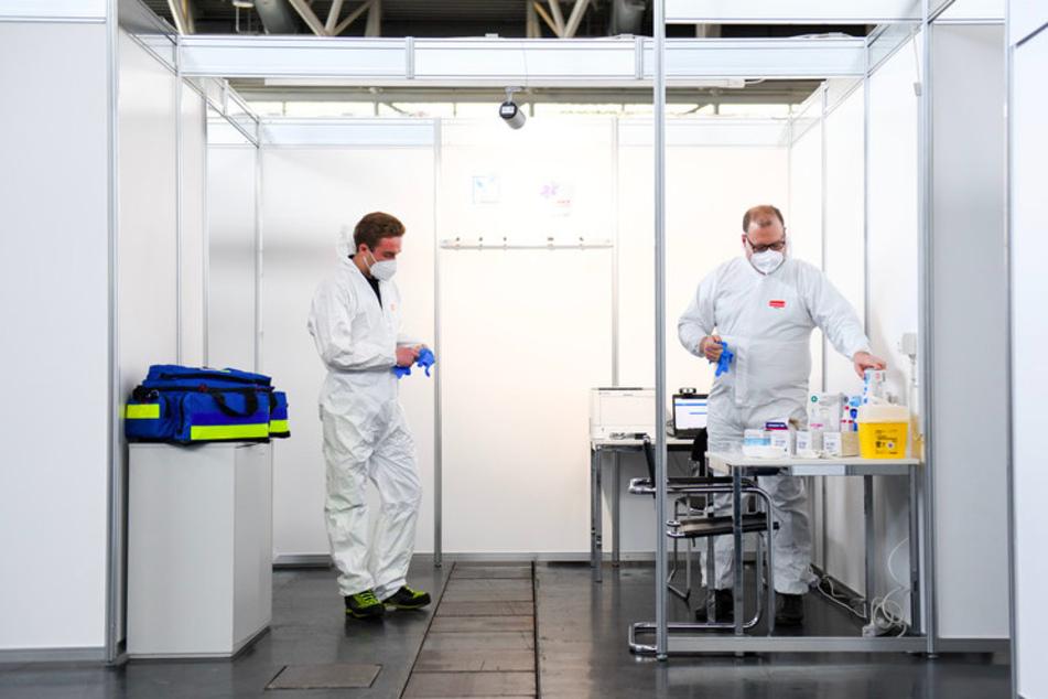 Ein Arzt und ein Mitarbeiter des Rettungsdienstes ziehen bei einem Pressetermin im neu eingerichteten Impfzentrum in der Messe München in einer Impfkabine Schutzkleidung an.