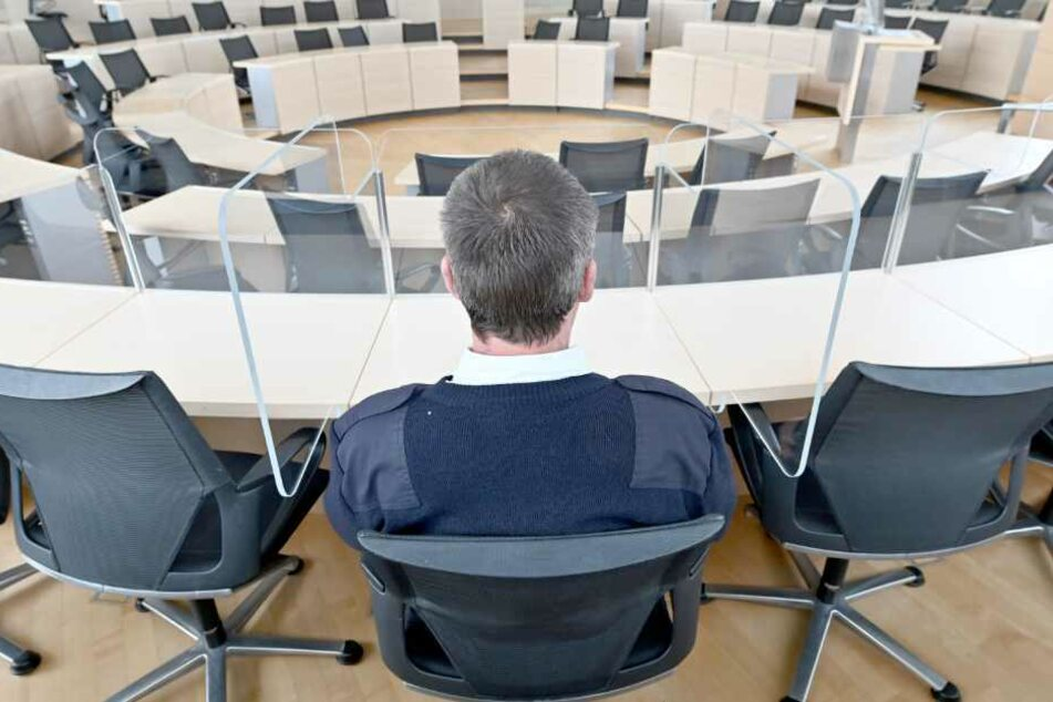 Ein Landtagsmitarbeiter sitzt zwischen den ersten Schutzwänden aus Plexiglas im Plenarsaal.