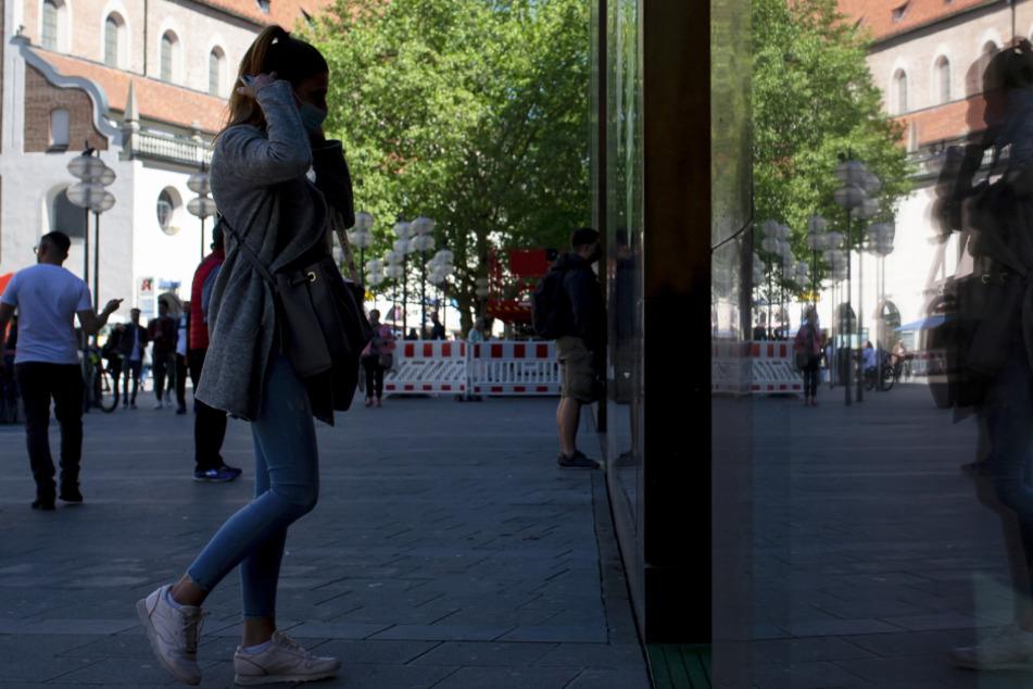 Passanten betreten in der Fußgängerzone in der Innenstadt ein Geschäft und spiegeln sich dabei in einer Fensterscheibe.