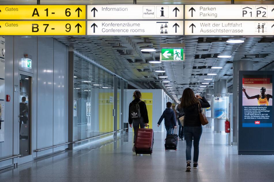 Fluggäste gehen durch das Abflugterminal im Flughafen Hannover.