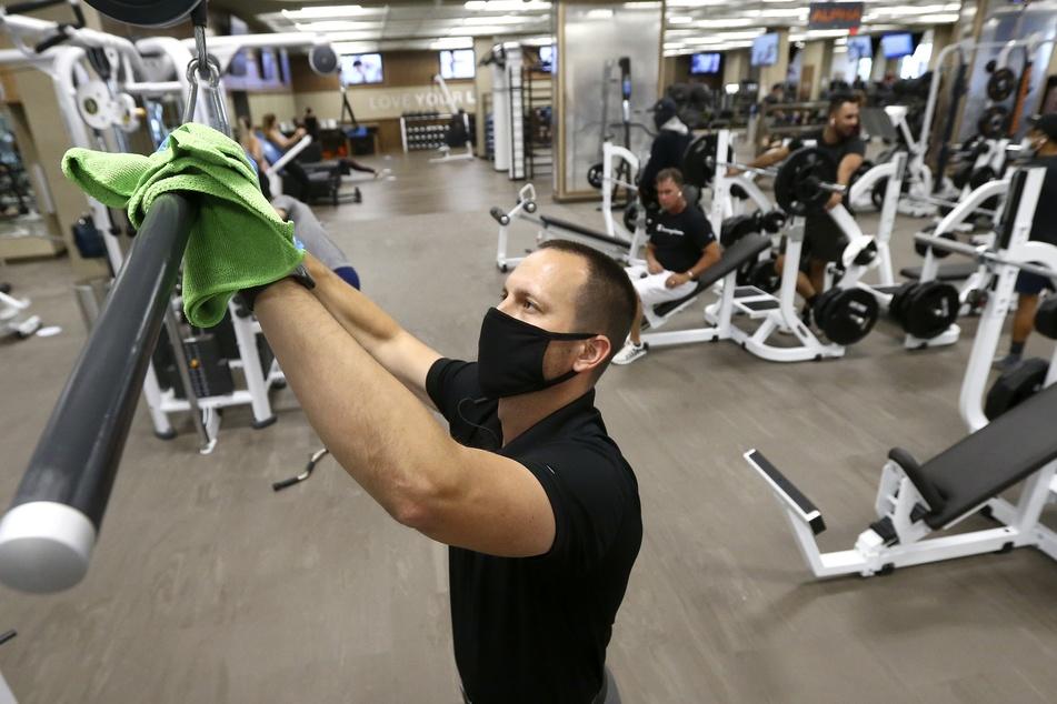 Ein Mitarbeiter desinfiziert ein Gerät im Fitnessstudio.