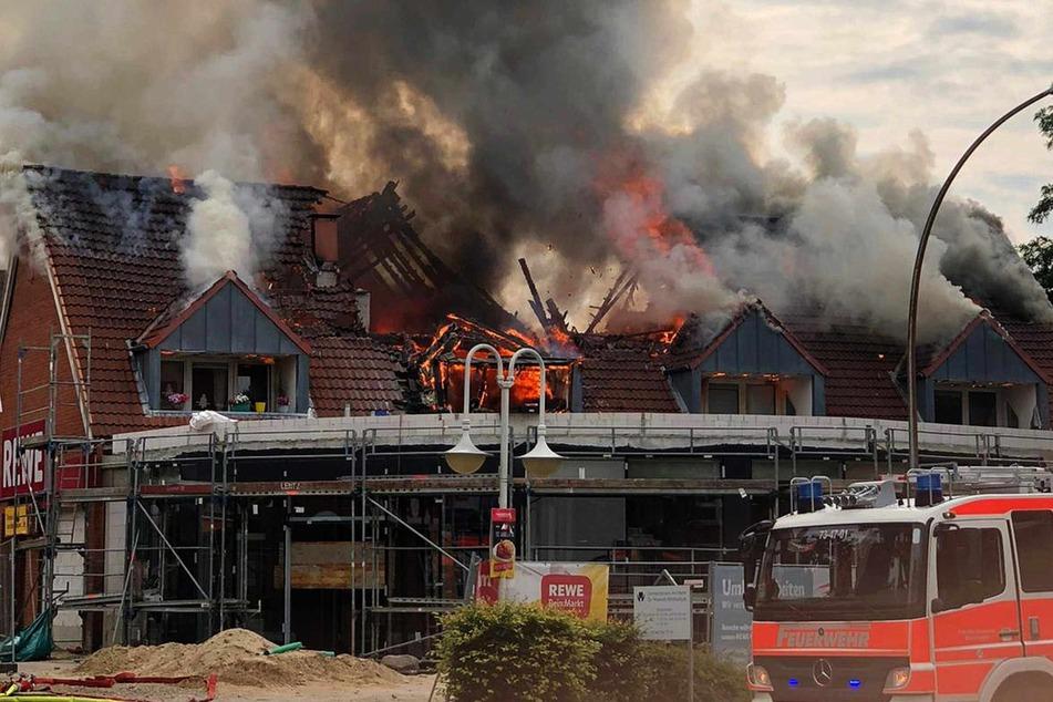 Der Dachstuhl über dem Rewe-Markt steht in Flammen.