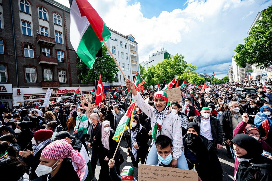 Teilnehmer der Demonstration verschiedener palästinensischer Gruppen gehen durch Neukölln.