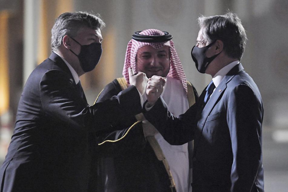 US-Außenminister Antony Blinken (59,r), wird von John Desrocher (l), Botschafter der USA in Katar, und Ibrahim Fakhroo, Direktor für Protokoll des Auswärtigen Amtes in Kabul, am Old Doha Flughafen begrüßt.